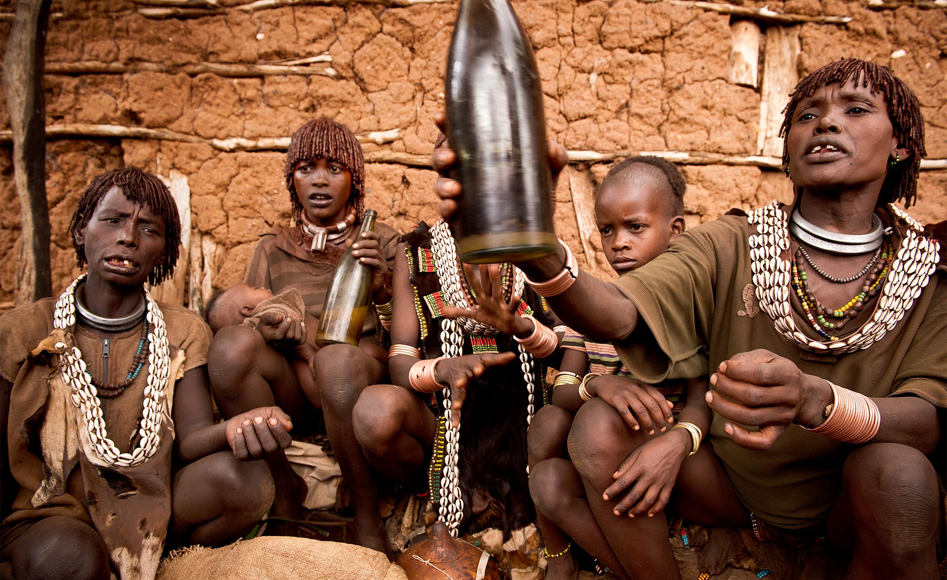 hammer tribe girls drinking beer at the local bar at dimeka market, omo valley ethiopia