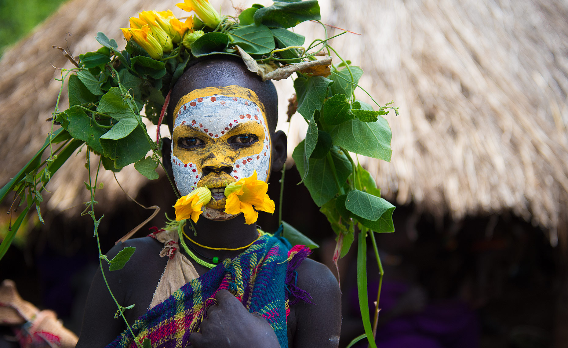 suri tribe boy with flowers and face paint omo park ethiopia